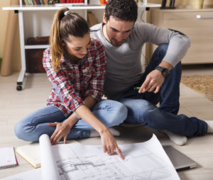 Young couple sitting on the floor and looking at the blueprint of new home.