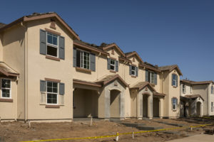 A row of townhomes in the final stages of construction, soon to be ready for sale.