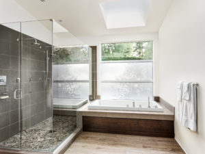 Large furnished bathroom in luxury home with tile floor, fancy cabinets, large mirror, and bathtub