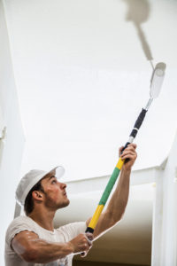 Closeup of Man Holding Roller Pin and Painting the Ceiling